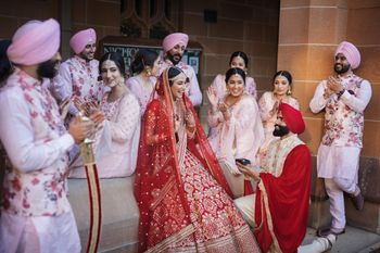 Photo of Candid shot of a groom proposing the bride with color-coordinated family members.