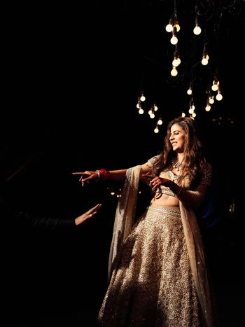 Photo of dancing bride shot in beige and gold lehenga on sangeet