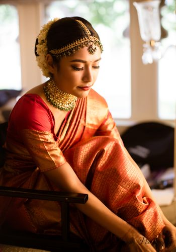 Photo of South Indian bride getting ready portrait in orange saree