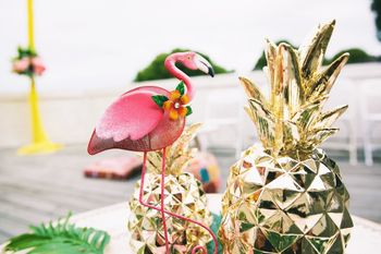 Photo of Tropical theme pineapple and flamingo centrepieces