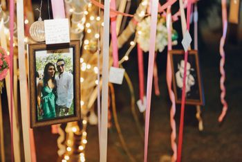 Photo of Couple photos hung from tree with ribbons. Guest leave wishes