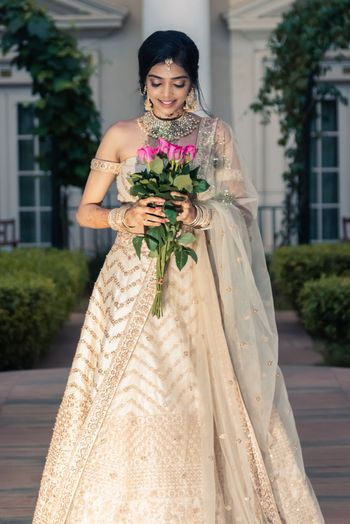 Photo of A bride in an ivory and gold lehenga with off-shoulder blouse and gold jewellery