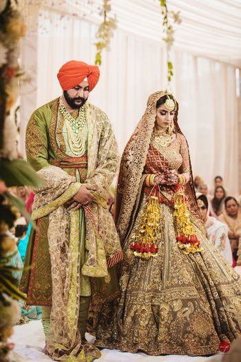 Photo of A Sikh bride and groom in coordinated, vintage-looking outfits