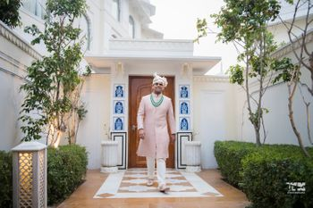 A groom in a pink sherwani and contrasting green accessories