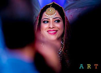Smiling Bride Wearing Gold Maangtikka