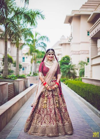 Maroon and gold bridal lehenga for winter wedding