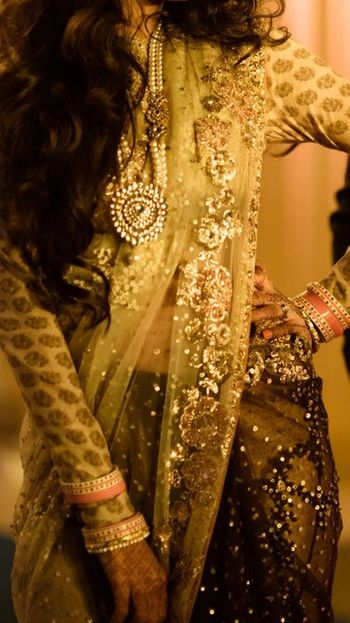 Photo of sabyasachi olive green sari with gold flower embrpidery and a printed gold blouse