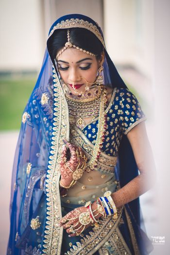 Photo of Bride in offbeat blue lehenga and gold jewellery
