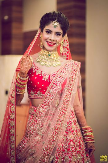 Photo of Bridal lehenga in red and pink with choker necklace