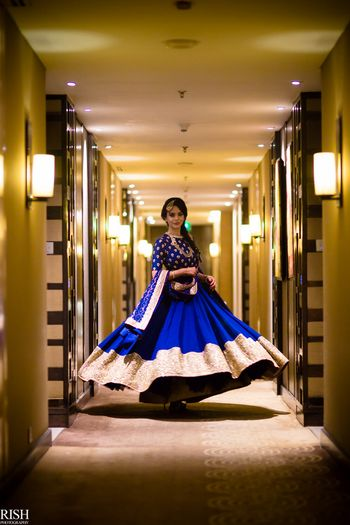 Bride twirling in blue and gold Sabyasachi lehenga