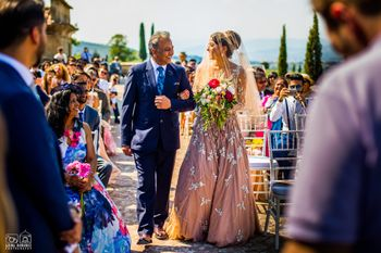 Offbeat bride in peach gown entering with her father