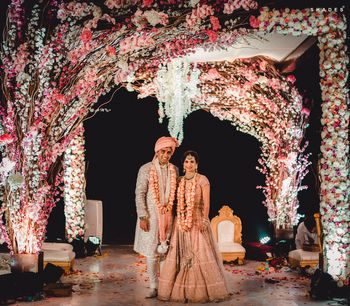 A couple poses at their unique floral mandap