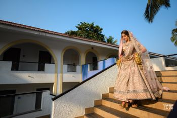 Photo of A bride walking down the stairs in a blush pink lehenga for her morning wedding