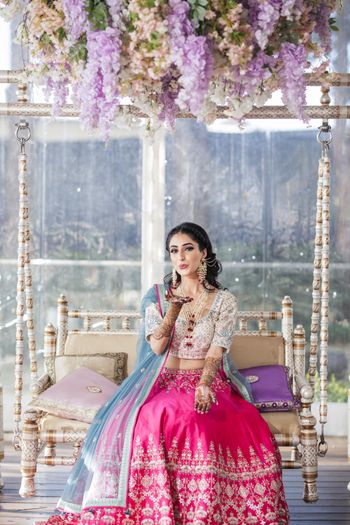 Bride wearing a pink and white lehenga with a blue dupatta on mehndi.