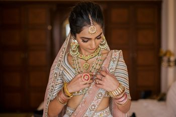 Photo of Bride wearing jewellery and fixing it