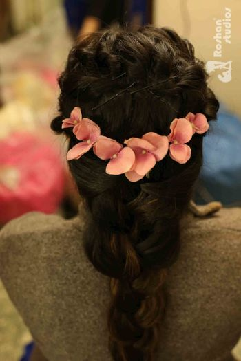 Mehendi hairdo with flowers for curly hair