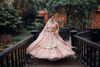Photo of A bride in a millennial pink lehenga twirling happily.