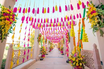mehendi entrance decor idea with tassels and florals