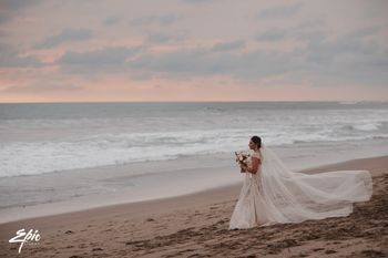 Bride on beach wearing gown with train