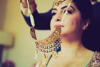 Photo of bride trying on necklace