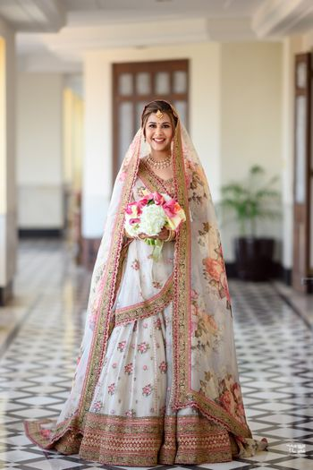 Bride in a beautiful white and pink floral lehenga