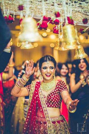 Bride dancing and entering under phoolon ki chadar with bells