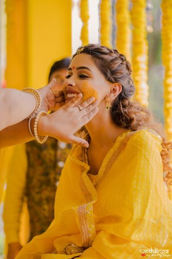 Photo of Bridal haldi portrait with people putting colour on her