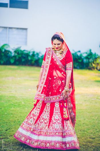 Photo of red bridal lehenga with pink border and white and gold zardozi detailing