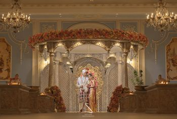 Photo of couple pose against grand south indian gold mandap
