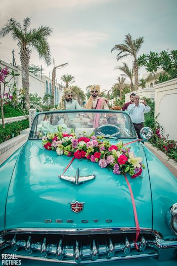 Photo of Groom entry idea in a blue vintage car