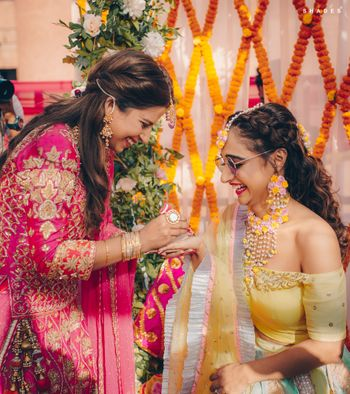 Photo of Bridesmaid applying mehndi on the bride's hand.