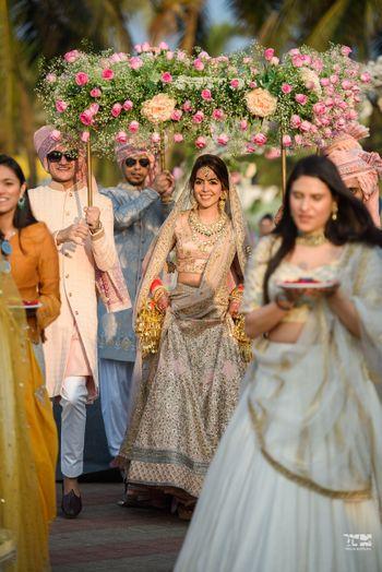 Photo of A bride ina  pink lehenga entering under a phoolon ki chadar