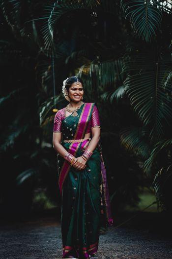 South indian bride wearing a dark green and purple kanjivaram saree on her wedding