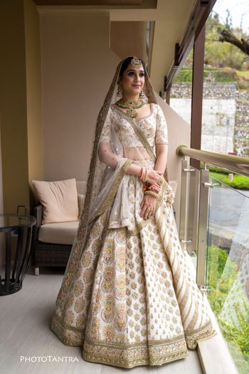 A bride in an ivory and gold lehenga with contrasting jewellery