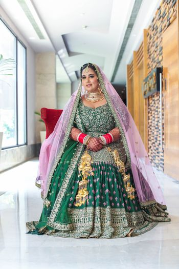 Photo of bride in a dark green anarkali with pink dupatta