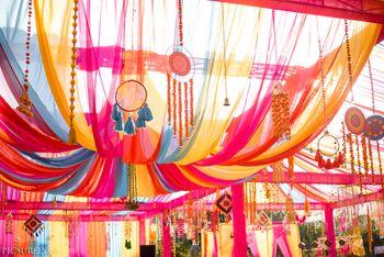 Mehendi decor idea with dreamcatchers hanging on tent drapes