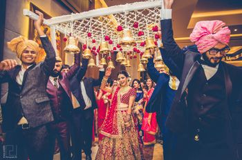 Photo of Bride under unique phoolon ki chadar with bells hanging
