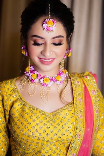 Photo of Bride wearing a yellow & pink lehenga with matching floral jewellery on her Mehendi