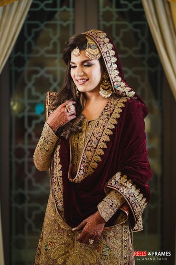 A bride in a maroon and gold velvet sharara