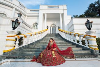 Bridal portrait on stairs with bride in red bridal lehenga