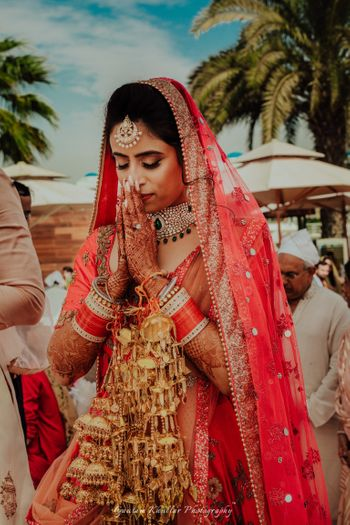 Pretty bridal portrait of an Indian bride wearing gold kaleere on her wedding