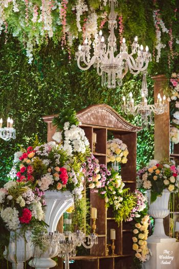 Photo of hanging floral decor and crystal chandelier for wedding