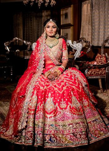 A bridal portrait captured with the bride in a bright pink and red ombre lehenga