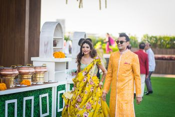 A bride and groom to be in yellow at their mehendi function