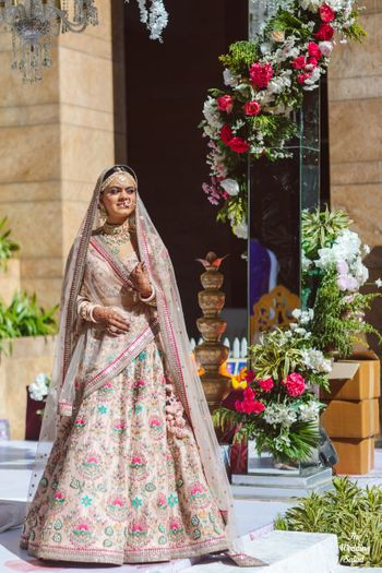 bride in a pastel pink sabyasachi lehenga with floral motifs