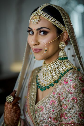 Pretty bride wearing an ivory lehenga with polki jewellery.