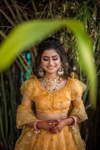 Mehendi bridal look inspiration with funky jewellery and ruffled blouse