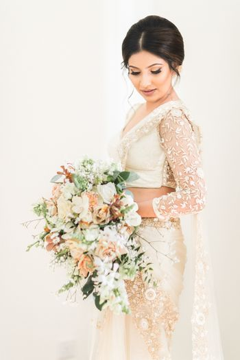 Photo of Bride in saree gown holding bouquet