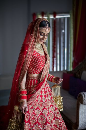 Photo of A bridal portrait on wedding day with the bride in a red Sabyasachi lehenga