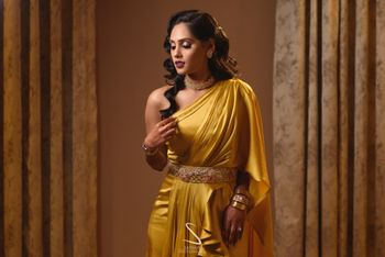 Photo of bride wearing a gold one shoulder gown and waistbelt